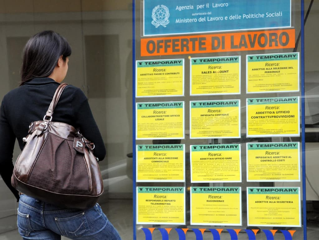 a woman stands in front of a window showing job postings in Italian